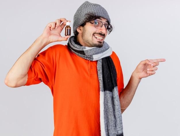 Freudiger junger kaukasischer kranker mann, der brille wintermütze und schal trägt, die medikament im glas zeigt, das auf seite zeigt, die auf weißer wand lokalisiert wird