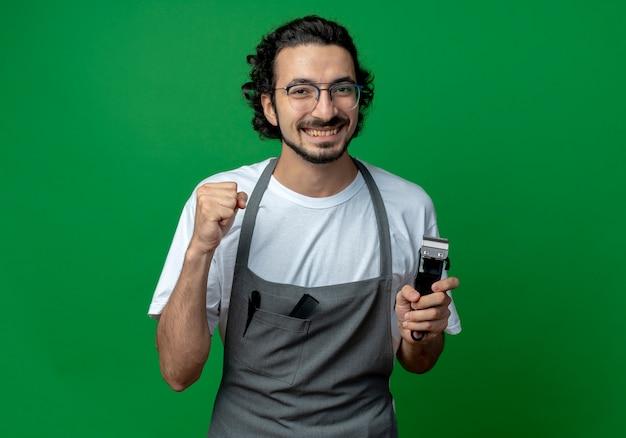 Freudiger junger kaukasischer männlicher friseur, der brille und welliges haarband in uniform hält, die haarschneidemaschinen und geballte faust lokalisiert auf grünem hintergrund mit kopienraum hält