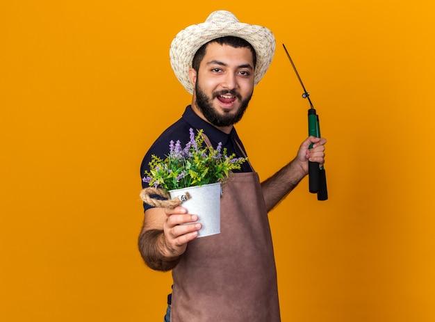 Freudiger junger kaukasischer männlicher gärtner, der gartenhut trägt, steht seitlich und hält gartenschere und blumentopf lokalisiert auf orange wand mit kopienraum