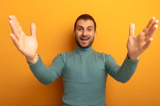 Freudiger junger kaukasischer mann, der kamera betrachtet, die hände lokalisiert auf orange hintergrund spreizt