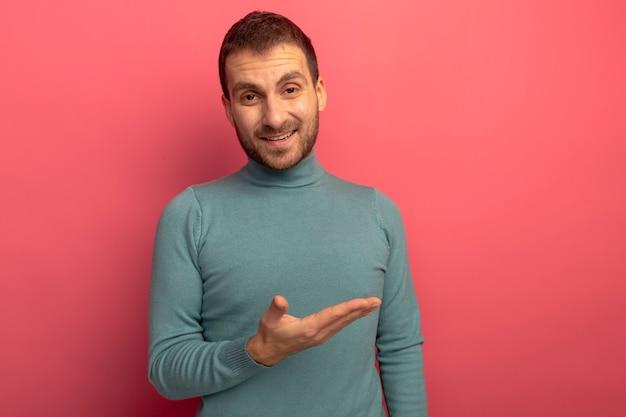 Freudiger junger kaukasischer mann, der kamera betrachtet, die zur seite mit hand lokalisiert auf purpurrotem hintergrund mit kopienraum zeigt Kostenlose Fotos