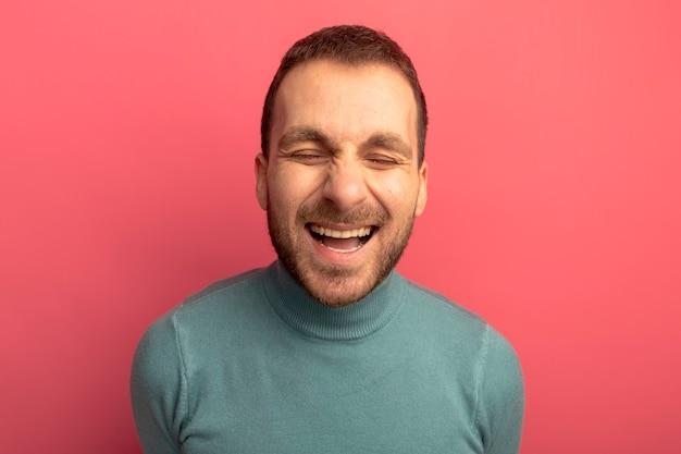 Freudiger junger kaukasischer mann, der mit geschlossenen augen lacht, die auf purpurrotem hintergrund lokalisiert werden Kostenlose Fotos