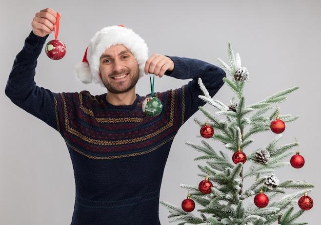 Freudiger junger kaukasischer mann, der weihnachtshut trägt, der nahe weihnachtsbaum steht und kamera betrachtet, die weihnachtsverzierungskugeln lokalisiert auf weißem hintergrund erhöht