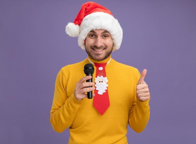 Freudiger junger kaukasischer mann, der weihnachtshut und krawatte hält, die mikrofon betrachten kamera hält, das daumen oben auf lila hintergrund zeigt