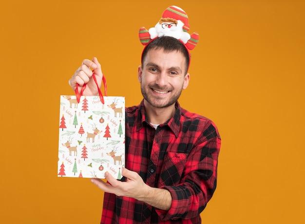 Freudiger junger kaukasischer mann, der weihnachtsmann-stirnband hält, das weihnachtsgeschenkbeutel betrachtet, der kamera lokalisiert auf orangefarbenem hintergrund betrachtet