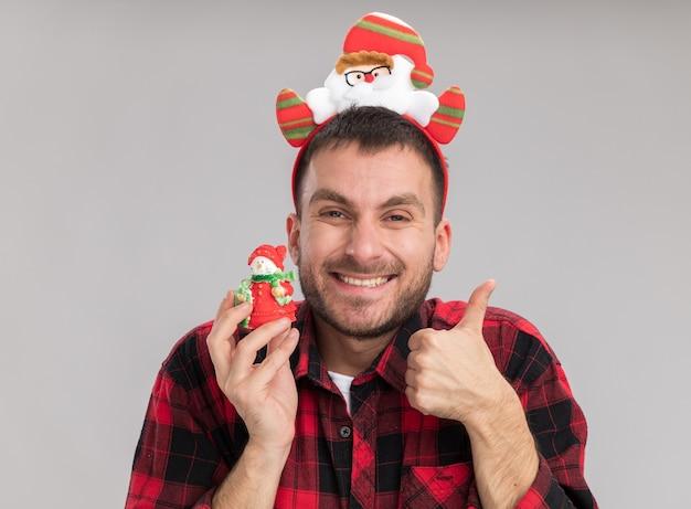 Freudiger junger kaukasischer mann, der weihnachtsmann-stirnband hält, der schneemann-weihnachtsverzierung betrachtet, die kamera zeigt, die daumen oben auf weißem hintergrund lokalisiert