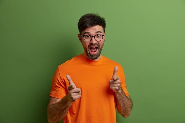 Freudiger junger kaukasischer mann mit bart macht fingerpistolengeste, zeigt auf sie, wählt jemanden aus, trägt optische brille und orange t-shirt, trifft wahl, isoliert auf grüner wand. du mein bruder
