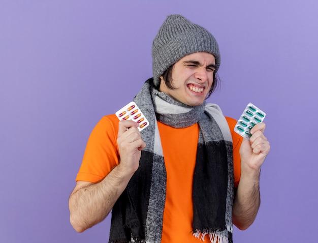Freudiger junger kranker mann, der wintermütze mit schal hält, der pillen lokalisiert auf purpur hält