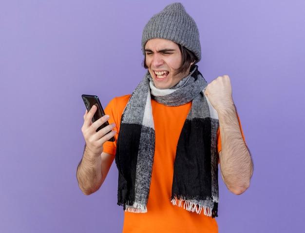 Freudiger junger kranker mann, der wintermütze mit schal hält und telefon betrachtet, das ja geste lokalisiert auf purpur zeigt