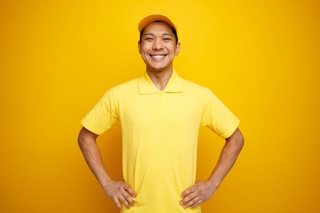 Freudiger junger lieferbote, der mütze und uniform trägt und hände auf taille hält