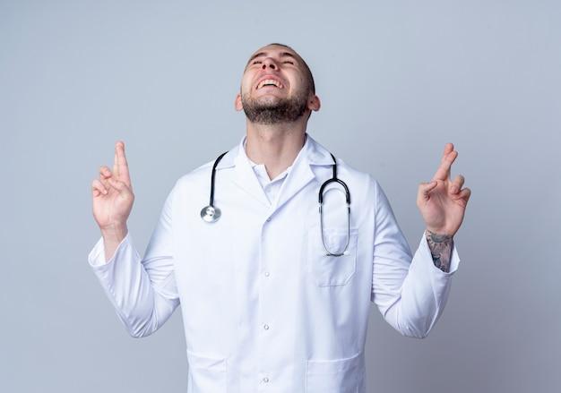 Freudiger junger männlicher arzt, der medizinische robe und stethoskop um seinen hals trägt und gekreuzte finger geste mit geschlossenen augen tut, die auf weiß isoliert werden