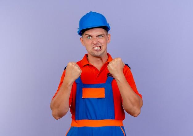 Freudiger junger männlicher baumeister, der uniform und schutzhelm trägt, der ja geste zeigt