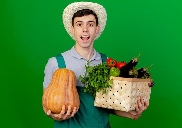 Freudiger junger männlicher gärtner, der gartenhut trägt, hält gemüsekorb und kürbis