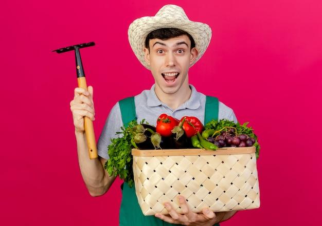 Freudiger junger männlicher gärtner, der gartenhut trägt, hält gemüsekorb und rechen