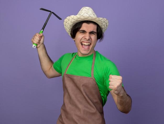 Freudiger junger männlicher gärtner in der uniform, die den gartenhut trägt, der hacke rechen erhöht, der ja geste zeigt