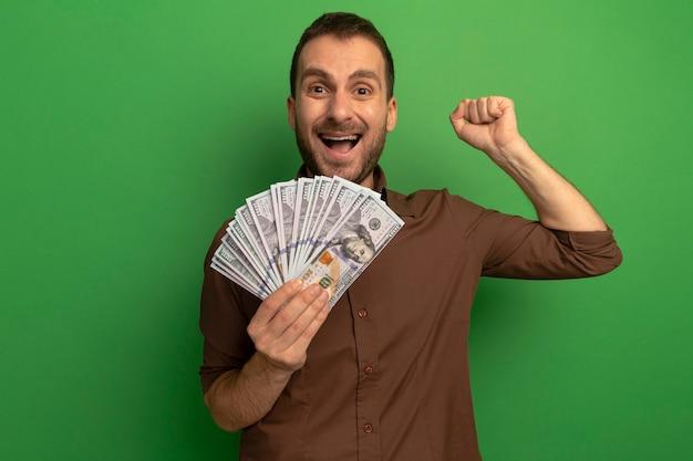 Freudiger junger mann, der geld hält, das vorne schaut, ja geste lokalisiert auf grüner wand tut