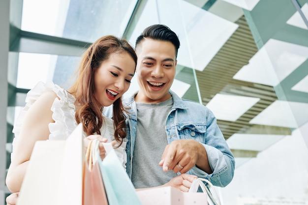 Freudiger junger mann und frau schauen in tasche mit einkäufen, die sie im einkaufszentrum gemacht haben