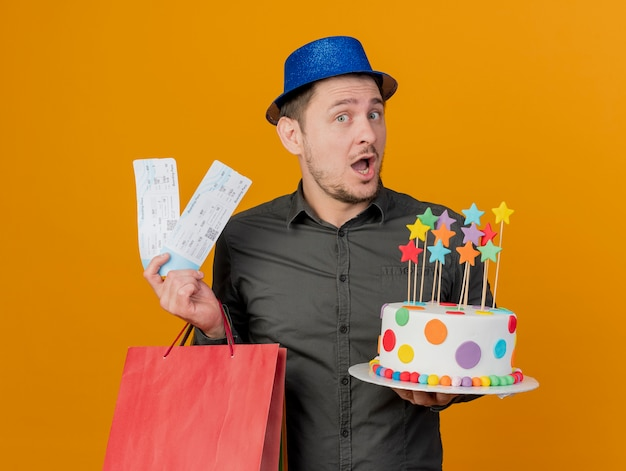 Freudiger junger party-typ, der blauen hut hält kuchen mit geschenktüte und tickets lokalisiert auf orange trägt