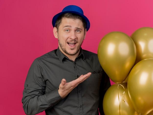 Freudiger junger party-typ, der blauen hut hält und mit hand auf ballons lokalisiert auf rosa zeigt