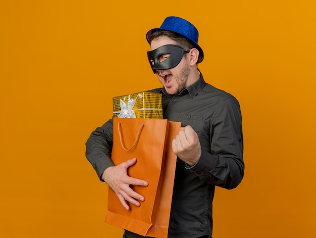 Freudiger junger party-typ, der blauen hut mit maskerade-augenmaske trägt, die geschenktüte hält, die ja geste lokalisiert auf orange zeigt