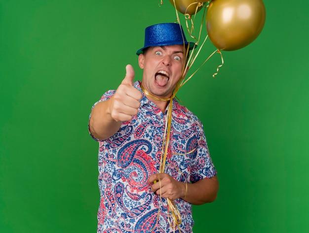 Freudiger junger party-typ, der blauen hut trägt, der ballons hält, die um den hals gebunden sind, zeigt daumen oben zeigt zunge isoliert auf grün