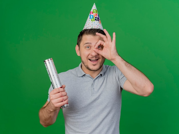 Freudiger junger party-typ, der geburtstagskappe hält, die konfettikanone hält, die auf grün lokalisierte blickgeste zeigt