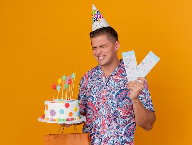 Freudiger junger party-typ, der geburtstagskappe hält kuchen mit geschenktüte und tickets lokalisiert auf orange trägt