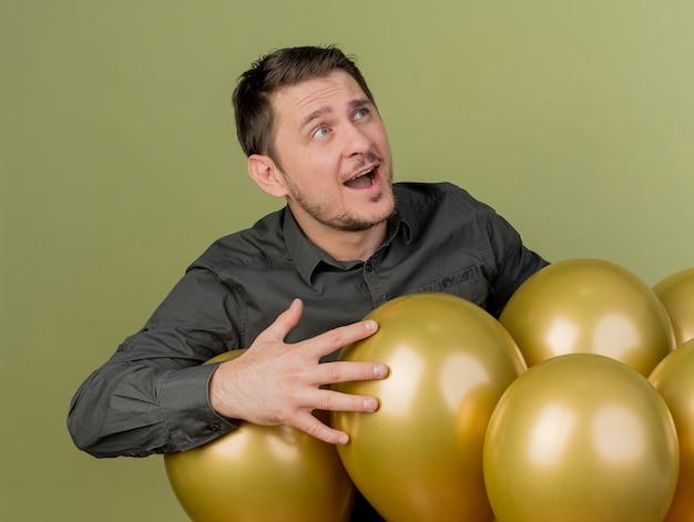 Freudiger junger party-typ, der schwarzes hemd trägt, das hinter luftballons steht, die auf olivgrün isoliert werden
