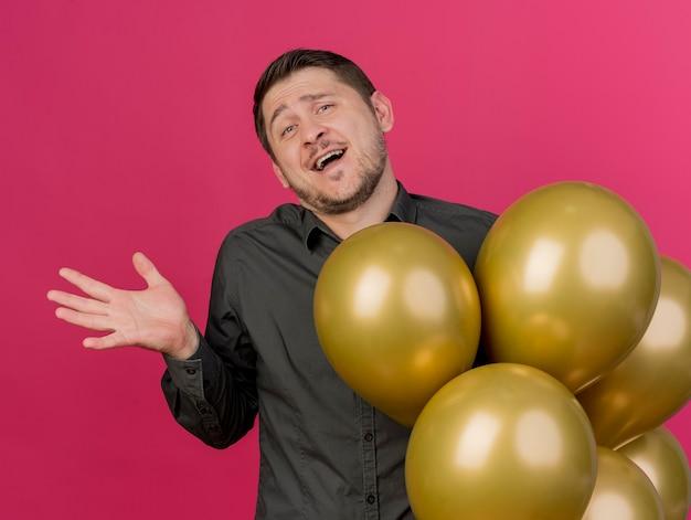 Freudiger junger party-typ, der schwarzes hemd trägt, das neben luftballons steht, die hand lokalisiert auf rosa verbreiten
