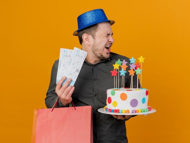 Freudiger junger party-typ mit geschlossenen augen, der blauen hut hält, der geschenktüte und kuchen mit den auf orange isolierten eintrittskarten hält