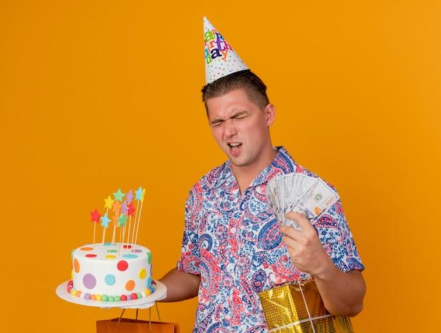 Freudiger junger party-typ mit geschlossenen augen, der geburtstagskappe hält, die geschenke mit kuchen und bargeld hält, die auf orange lokalisiert werden