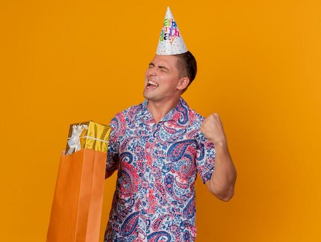 Freudiger junger party-typ mit geschlossenen augen, der geburtstagskappe hält, die geschenktüte hält, die ja geste lokalisiert auf orange zeigt
