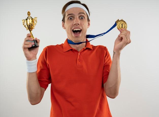 Freudiger junger sportlicher kerl, der stirnband mit armband hält gewinnerpokal mit medaille lokalisiert auf weißer wand trägt