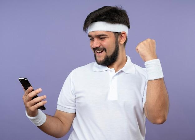 Freudiger junger sportlicher mann, der stirnband und armband hält und telefon betrachtet, das ja geste zeigt
