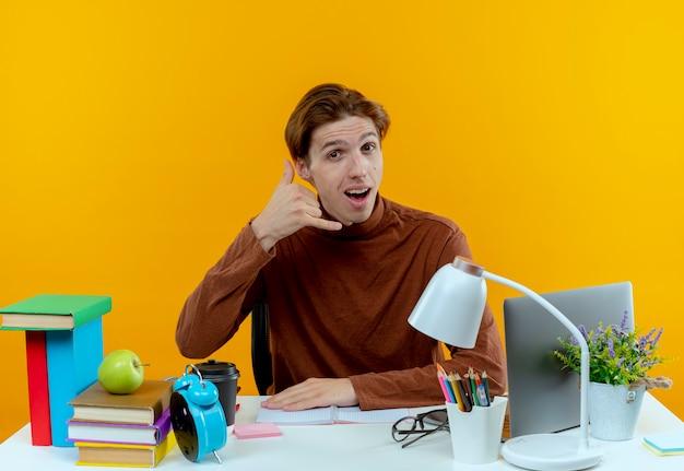 Freudiger junger studentenjunge, der am schreibtisch mit schulwerkzeugen sitzt, die telefonanrufgeste zeigen