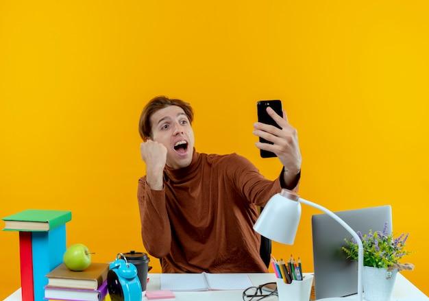 Freudiger junger studentjunge, der am schreibtisch mit den schulwerkzeugen sitzt, die telefon halten und betrachten und ja geste zeigen