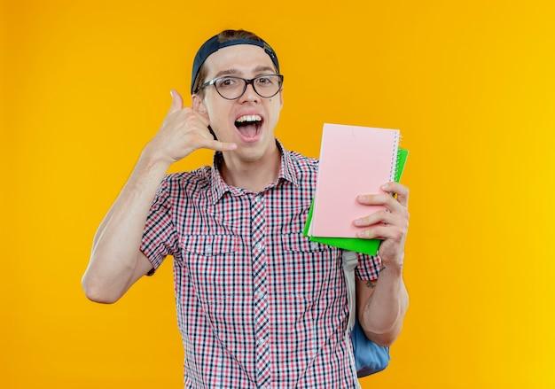 Freudiger junger studentjunge, der brille und kappe hält, notizbuch hält und telefonanrufgeste zeigt