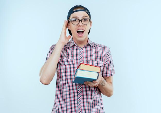 Freudiger junger studentjunge, der brille und kappe trägt bücher hält und hand auf ohr legt