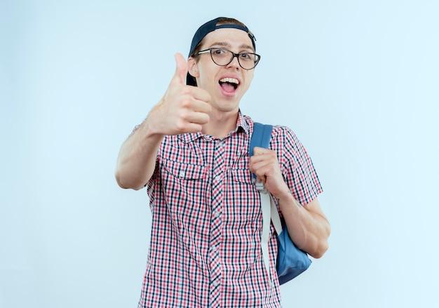 Freudiger junger studentjunge, der rucksack und brille trägt und seinen daumen hochkappt