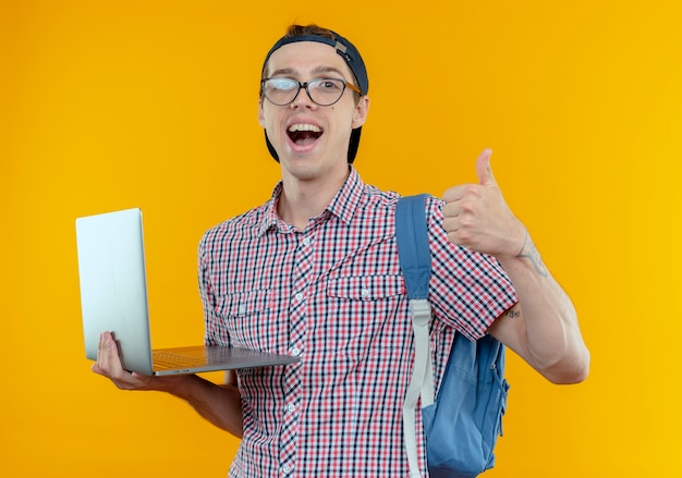 Freudiger junger studentjunge, der rückentasche und brille und kappe trägt laptop seinen daumen hoch hält