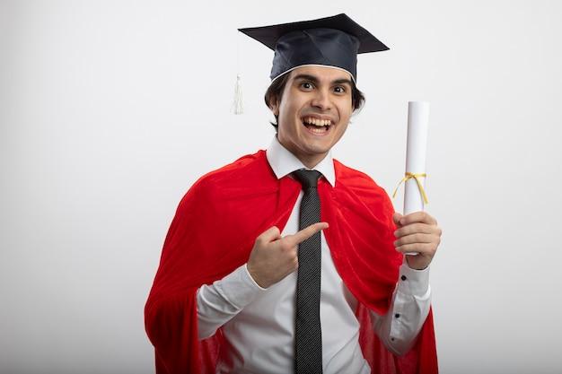 Freudiger junger superheld, der krawatte und abschlusshut hält und punkte auf diplom zeigt