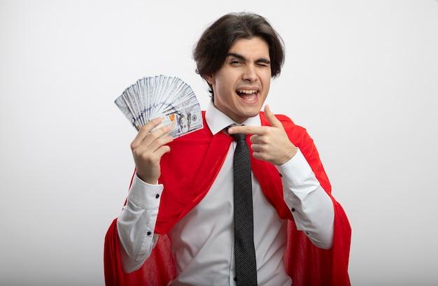Freudiger junger superheld, der krawattenhaltung trägt und auf bargeld lokalisiert auf weiß zeigt