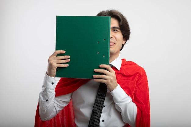 Freudiger junger superheld kerl, der krawatte bedecktes gesicht mit klemmbrett trägt und zunge lokalisiert auf weißem hintergrund zeigt