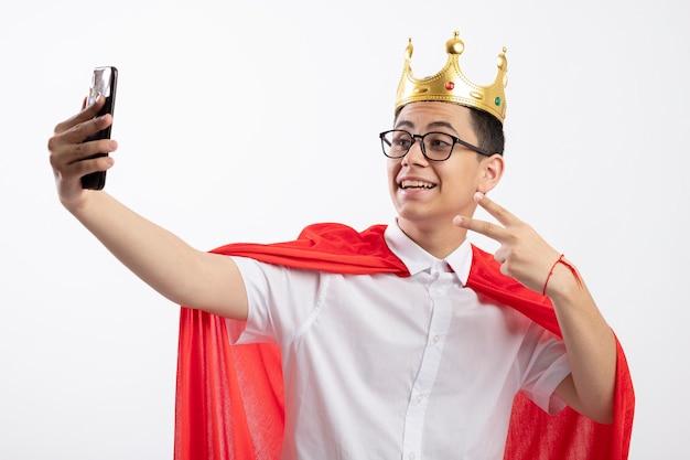 Freudiger junger superheldenjunge im roten umhang, der brille und krone trägt, die friedenszeichen tun, das selfie lokalisiert auf weißem hintergrund nimmt