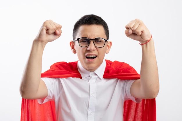 Freudiger junger superheldenjunge im roten umhang, der die brille trägt, die kamera betrachtet, die fäuste anhebt, die sieg lokalisiert auf weißem hintergrund genießen
