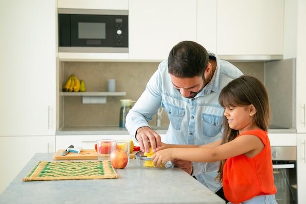 Freudiger junger vater und tochter genießen das gemeinsame kochen. mädchen und ihr vater drücken zitronensaft an der küchentheke. familienkochkonzept