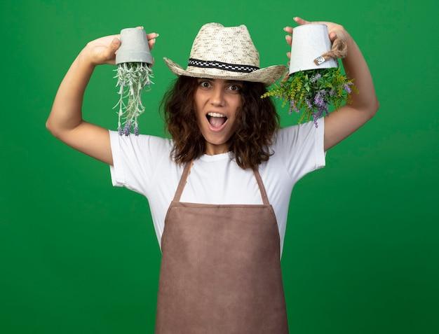 Freudiger junger weiblicher gärtner in der uniform, die gartenhut trägt, der oben unten blumen in blumentöpfen hält