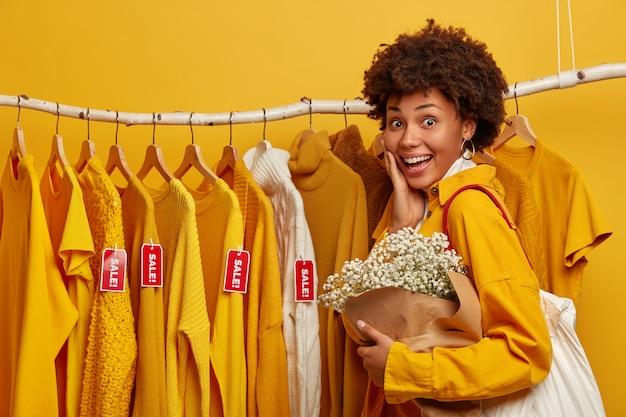 Freudiger käufer der lockigen haare wählt kleidung zum verkauf, die an gestellen hängt, trägt tasche, stellt mit blumenstrauß, lokalisiert über gelbem hintergrund.