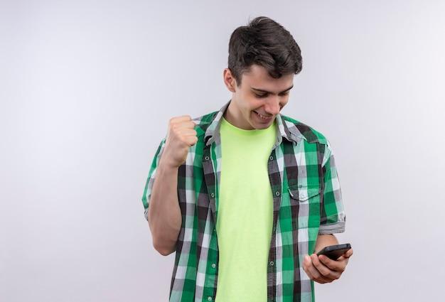 Freudiger kaukasischer junger mann, der grünes hemd trägt, das telefon auf seiner hand schaut und ja-geste auf isolierter weißer wand zeigt