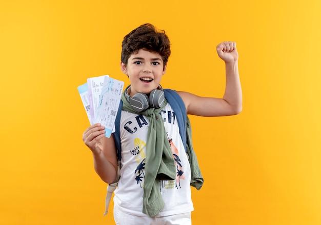 Freudiger kleiner schuljunge, der rückentasche und kopfhörer trägt, die karten halten und ja-geste lokalisiert auf gelbem hintergrund zeigen